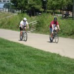Two cyclists ride along the Riverwalk in Louisville's Waterfront Park.