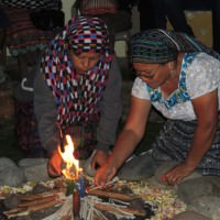 Two women light the fire for the b'ak'tun ceremony. The colored candles represent the four elements of Earth: fire, air, water and earth.
