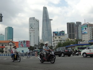 Traffic in Saigon with the Bitexco Financial Tower in the background.