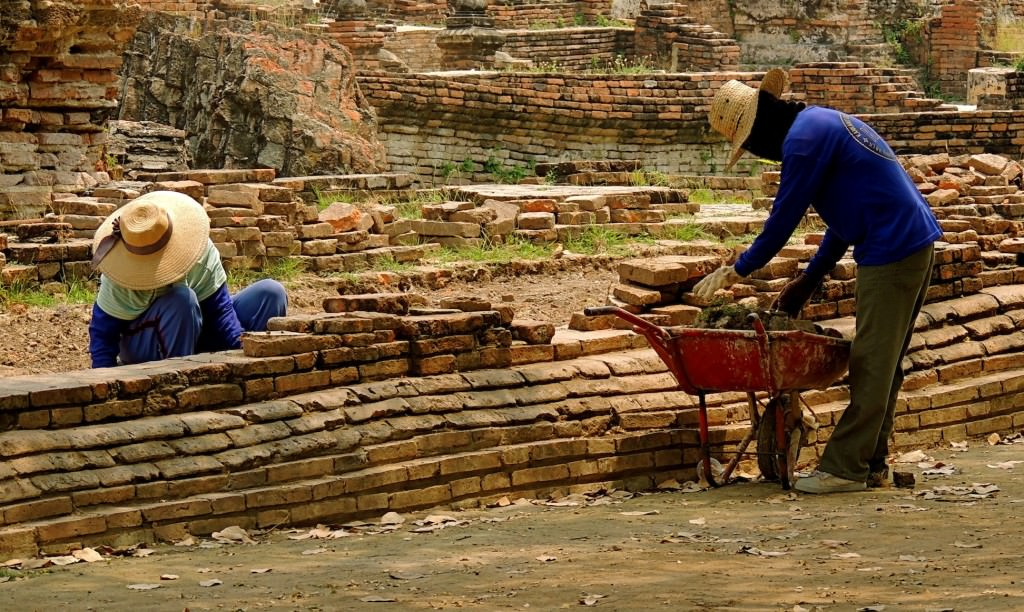 Workers build walls in front of the chedis.
