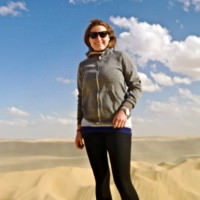 Andrea Boland poses for a picture with Egyptian sand dunes. She spent two months in the country.